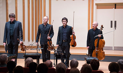 The Quatuor Danel ensemble string quartet standing with their instruments