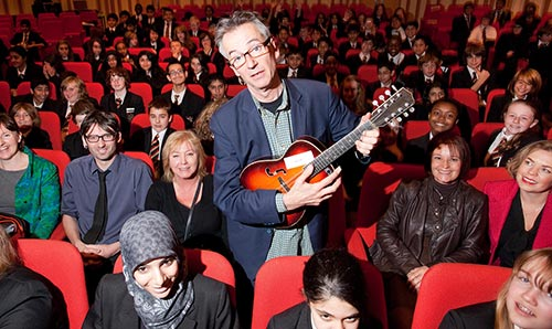 John Hegley performing in the Cosmo Rodewald Concert Hall for school groups.